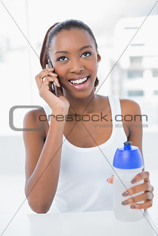 Smiling athletic woman having a phone call