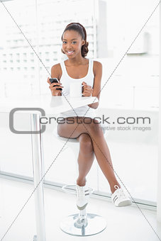 Smiling athletic woman holding smartphone