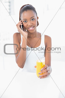 Happy athletic woman phoning holding orange juice