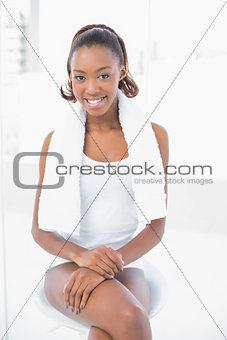 Smiling athletic woman wearing towel on shoulders