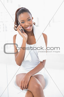 Smiling athletic woman wearing towel on shoulders phoning