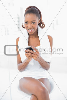 Smiling athletic woman wearing towel on shoulders text messaging