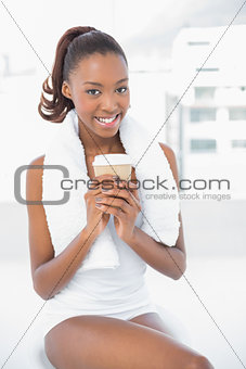 Smiling athletic woman holding coffee