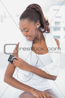 Smiling athletic woman changing music on her mp3
