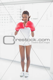 Slender athletic woman wearing boxing gloves
