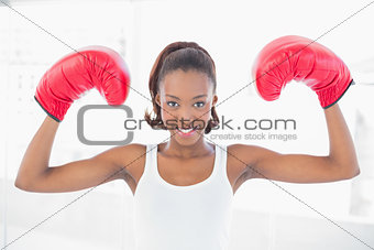Slender athletic woman wearing boxing gloves making victorious gesture
