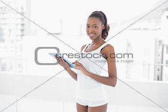 Fit pretty woman holding digital tablet