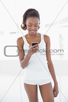 Fit cheerful woman text messaging
