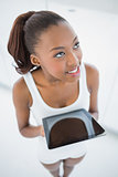 High angle view of cheerful sporty woman holding tablet