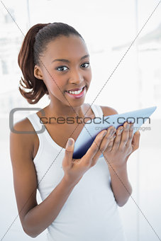 Smiling sporty woman holding tablet