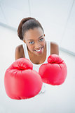 High angle view of cheerful fit woman with red boxing gloves