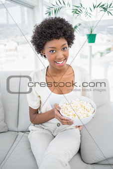 Attractive brunette holding popcorn sitting on cosy sofa