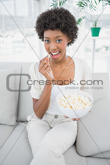 Attractive brunette eating popcorn sitting on cosy sofa
