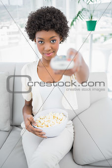 Attractive brunette holding popcorn while watching tv