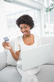 Smiling gorgeous woman using her credit card to buy online