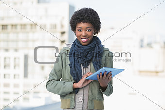 Smiling casual woman holding tablet pc