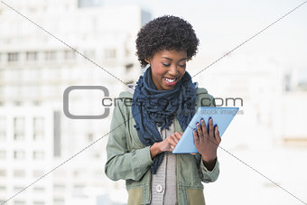 Smiling casual woman using tablet pc