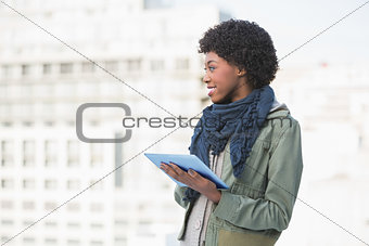 Cheerful casual woman holding tablet pc