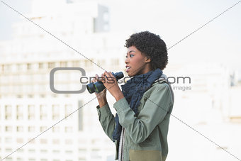 Curious casual model holding binoculars
