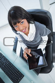 High angle view of cheerful businesswoman holding tablet