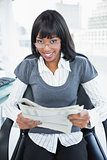 Happy businesswoman holding newspaper