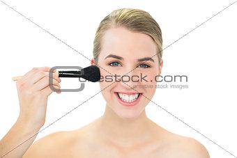 Smiling attractive blonde using blusher brush