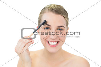 Smiling attractive blonde using eyebrow brush