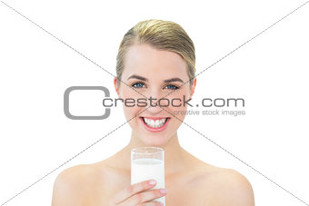 Smiling attractive blonde holding glass of milk