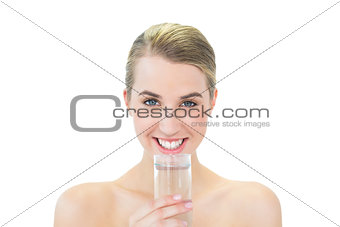 Smiling attractive blonde holding glass of water