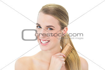 Smiling attractive blonde combing her hair
