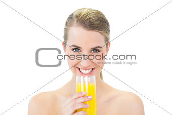 Smiling attractive blonde holding glass of orange juice