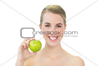 Smiling attractive blonde holding green apple