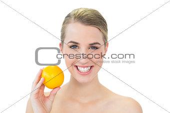 Smiling attractive blonde holding orange
