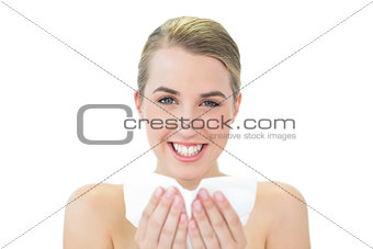 Smiling attractive blonde blowing her nose