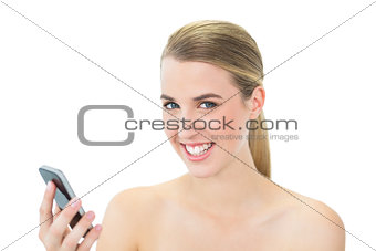 Smiling attractive blonde holding her smartphone