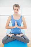 Peaceful attractive blonde relaxing in lotus position