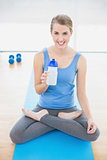 Cheerful pretty blonde in lotus position holding flask