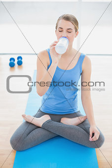 Cheerful pretty blonde in lotus position drinking water