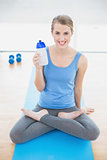 Smiling pretty blonde in lotus position holding flask