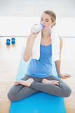 Peaceful pretty blonde in lotus position drinking water