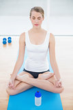 Relaxed sporty woman in lotus position posing