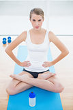Serious sporty woman in lotus position posing