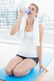 Fit woman on her knees on sport mat drinking water