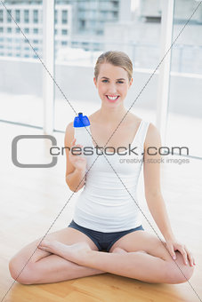 Cheerful fit woman in lotus position holding flask