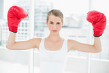 Competitive fit woman with red boxing gloves cheering up