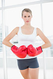 Competitive woman with red boxing gloves posing
