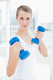 Sporty pretty woman exercising with dumbbells