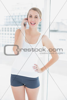 Cheerful sporty woman on the phone
