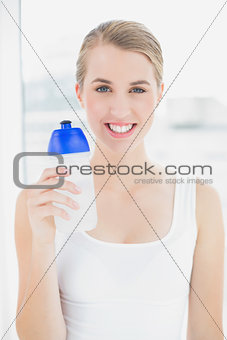 Happy sporty woman holding flask