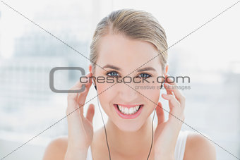 Close up on smiling sporty woman listening to music